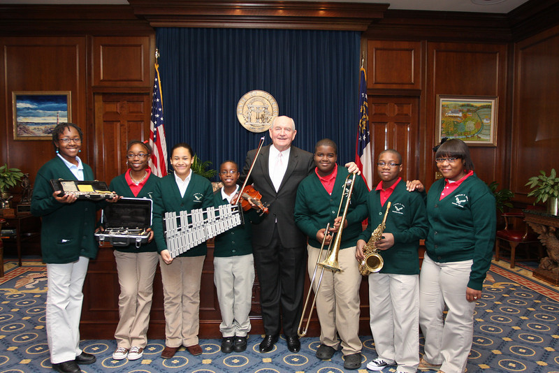 Governor Sonny Perdue poses with band students who have just received new musical instruments during a Gift Day donation.