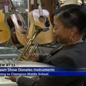 Rep. of Champion Middle School holding a donated trumpet at Uncle Sam's Pawn Shop